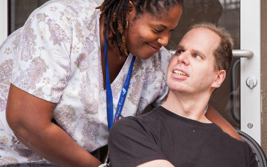 Enhanced Living caregiver and man smiling at each other
