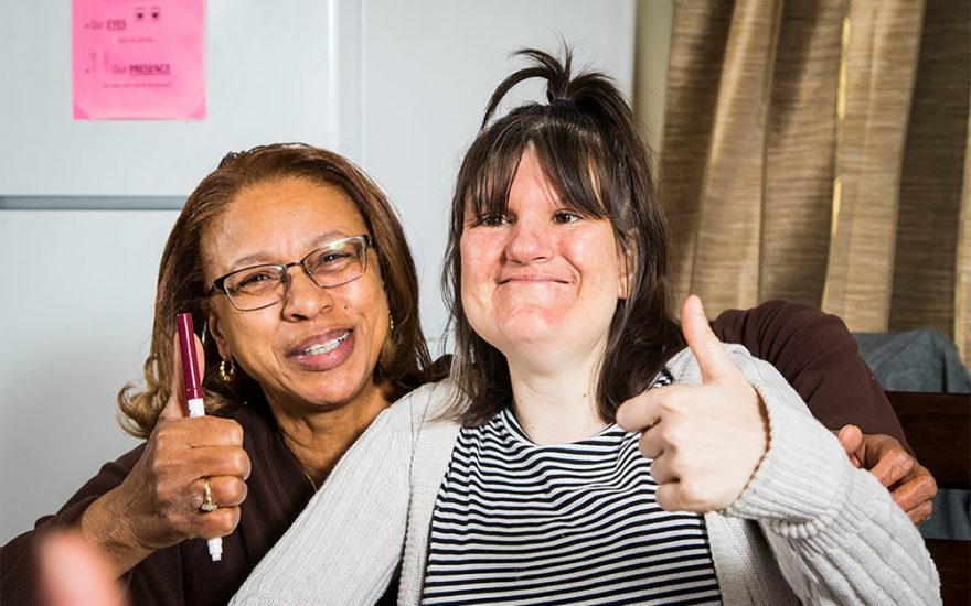 Enhanced Living caregiver and woman giving thumbs up