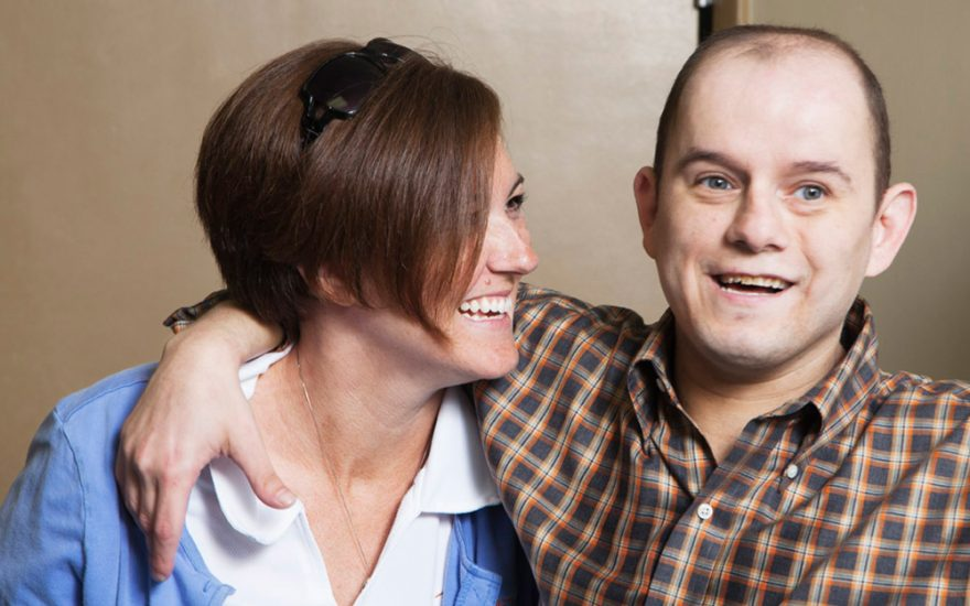 Enhanced Living caregiver and man with his arm around her shoulder