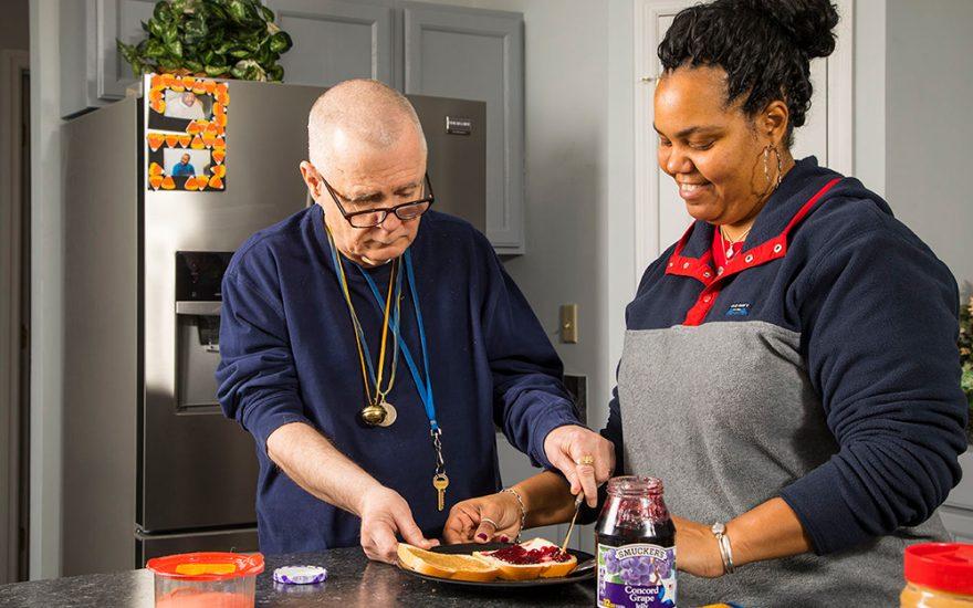 Enhanced Living caregiver and man making lunch together