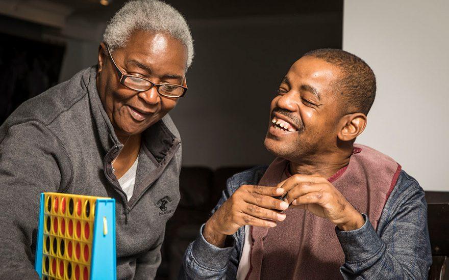 Enhanced Living caregiver and man smiling