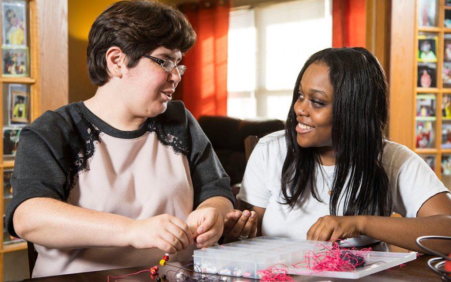 Enhanced Living caregiver and woman beading