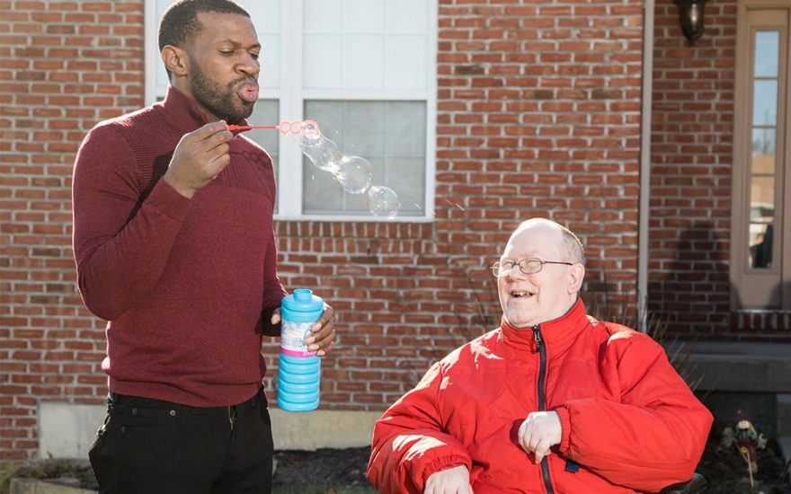 Enhanced Living caregiver and man blowing bubbles