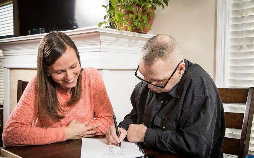 Enhanced Living caregiver and man drawing