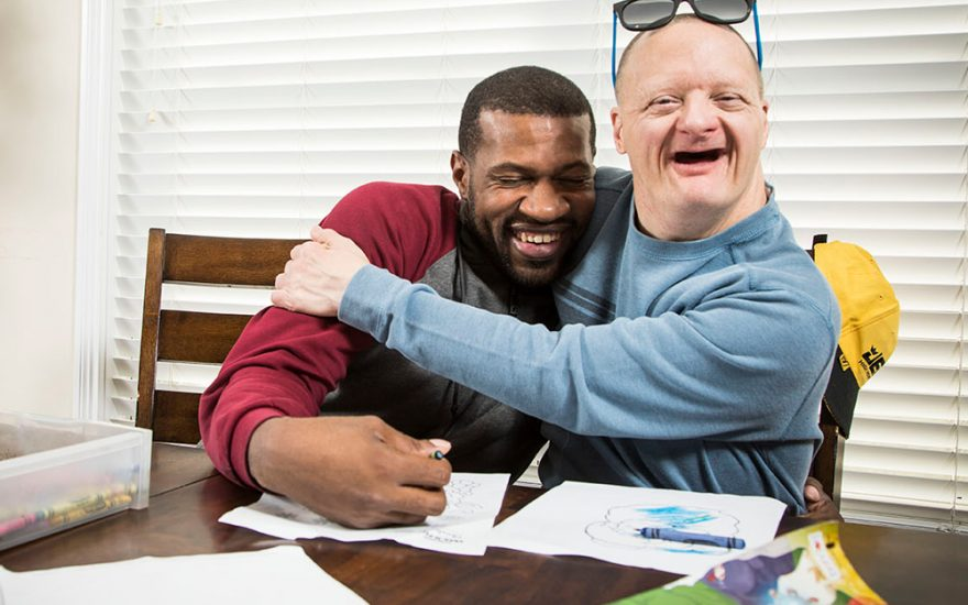 Enhanced Living caregiver and man hugging