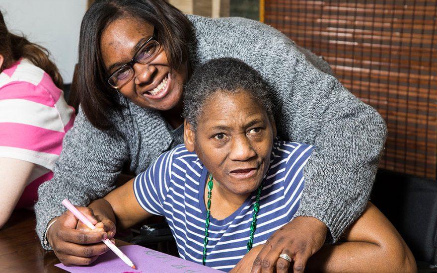 Enhanced Living caregiver and woman smiling